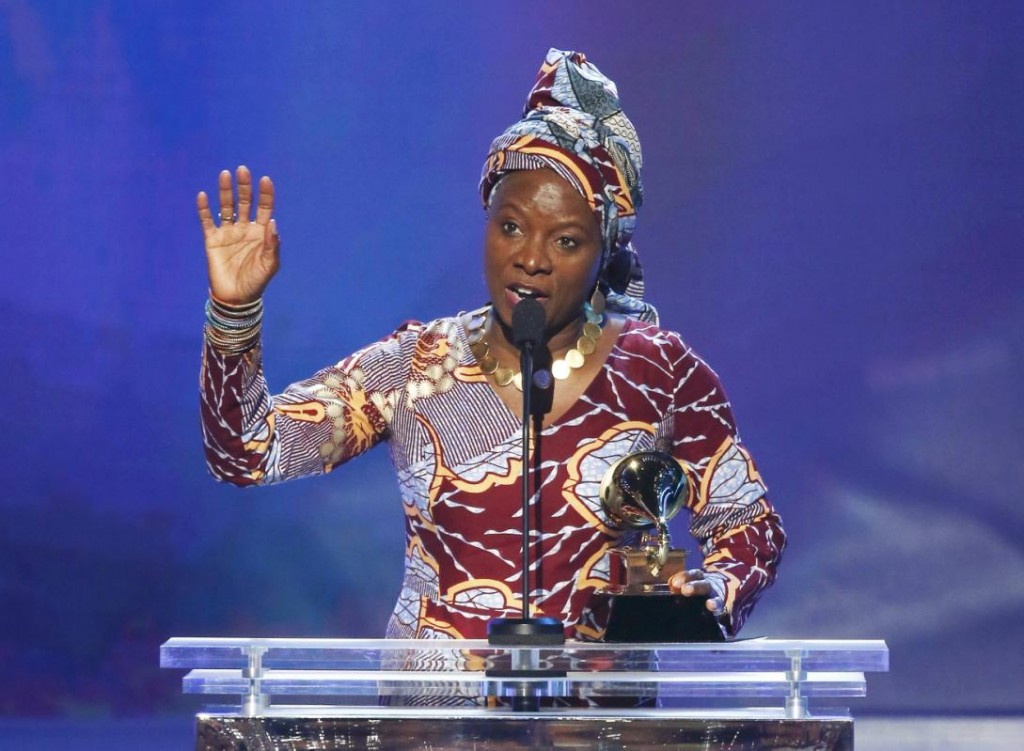 "Angelique Kidjo accepts the award for best world music album for ""Eve"" from presenter Hunter Hayes during the pre-telecast awards at the 57th annual Grammy Awards in Los Angeles"